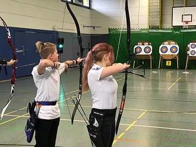2 jugendlische Schützen spannen den Bogen bei einem Turnier