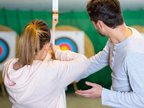 Trainer korrigiert eine Frau beim umgang mit dem Bogen